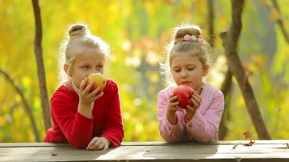 Two little girls eating a natural apples ,outdoors . Two little girls eating a natural apples