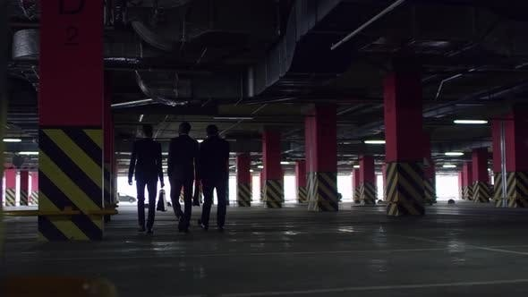 Thumbnail for Silhouettes of Businessmen Walking in Parking Lot