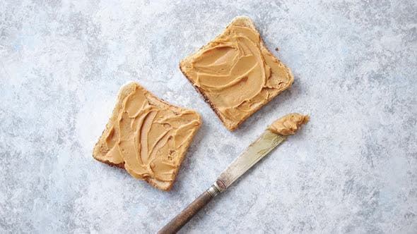 Thumbnail for Two Tasty Peanut Butter Toasts Placed on Stone Table