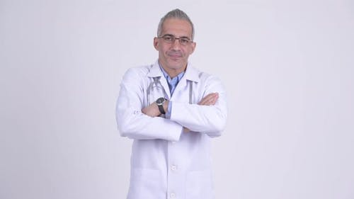 Happy Persian Man Doctor with Arms Crossed Against White Background