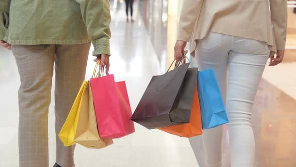Legs of Shopaholics with Shopping Bags Walking Down Mall. Slow-motion. Female Women Walking at