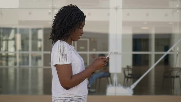 Thumbnail for Side View of Smiling African American Woman Using Smartphone