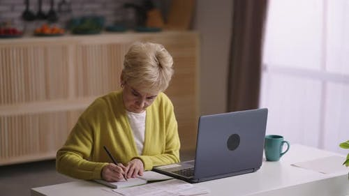 Old Woman is Learning Online Sitting at Home Kitchen with Laptop Looking for Information in Internet