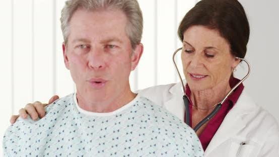 Senior doctor listening to elderly patient breathing