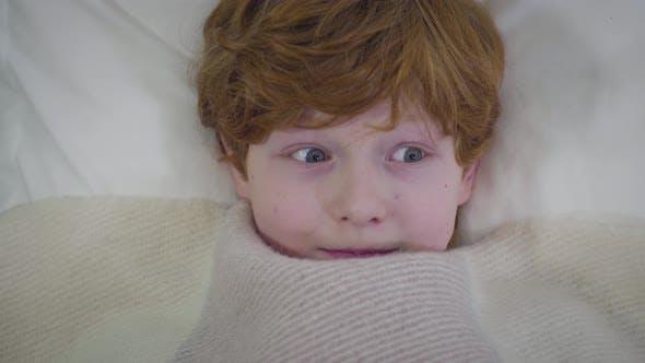 Thumbnail for Nahaufnahme von Rothaarigen Kaukasischen Jungen mit grauen Augen unter Decke liegen und umschauen