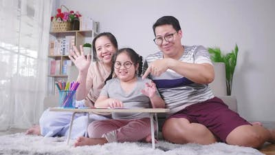 Happy family looking at camera in living room