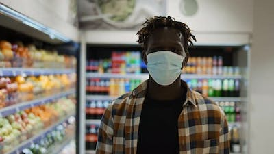 African American Man in Mask Walks By Supermarket