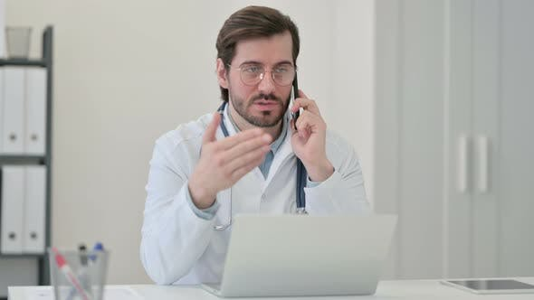 Thumbnail for Young Male Doctor Laptop Talking Smartphone