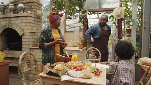 Afro-American Family Gathering for Dinner in Greenhouse