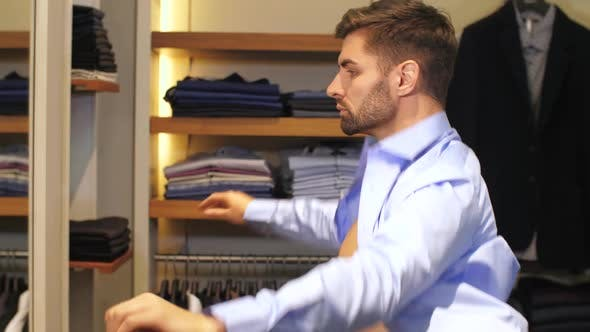 Thumbnail for Man Tries on a Shirt in a Boutique