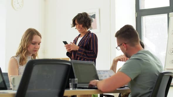 Woman Showing Smartphone To Colleagues at Office