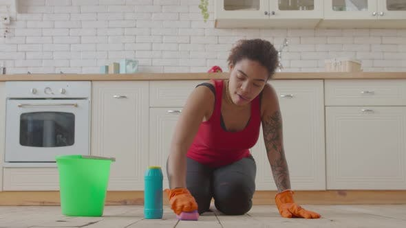 Thumbnail for Kneeling African Woman Wiping Floor with Detergent