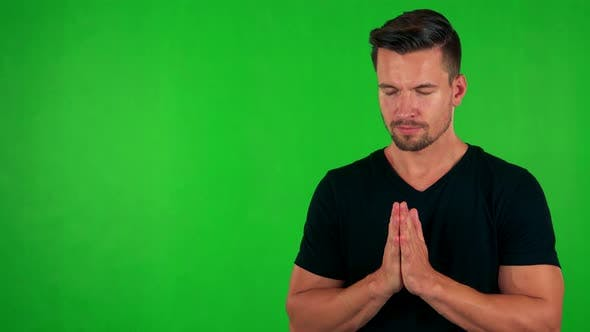 Cover Image for Young Handsome Caucasian Man Prays - Green Screen - Studio