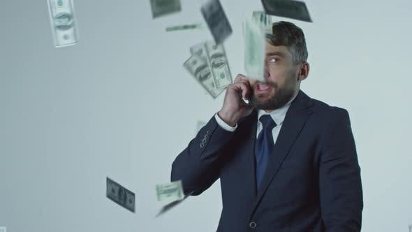 Thumbnail for Dollars Falling on Businessman Talking on Mobile Phone