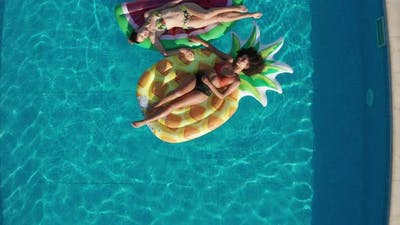 Drone Shot of Relaxed Women on Floaties in Pool