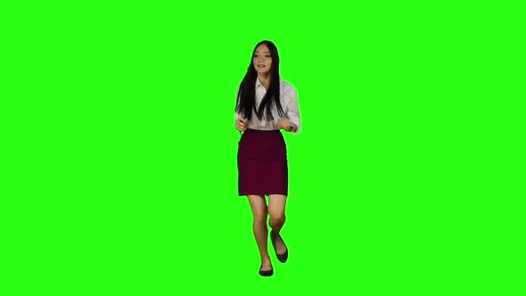 Thumbnail for Asian Girl Walking Along the Road, Looking at the Clock Starts To Run. Green Screen. Slow Motion