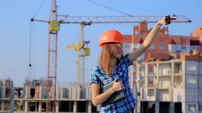 Young female engineer on the radio coordinates the progress