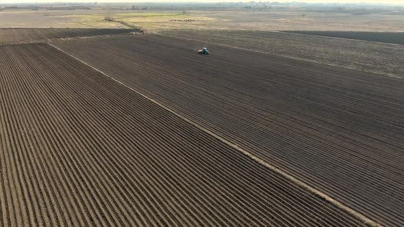 Thumbnail for Tractor Working on Large Brown Fields