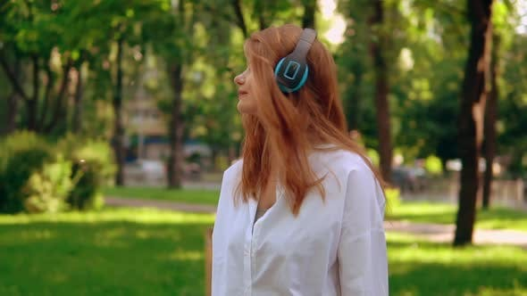 Thumbnail for Woman Using Headphones Listening Music Outdoors