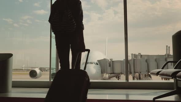 Cover Image for A Woman with Luggage Goes To a Large Window in the Airport Terminal