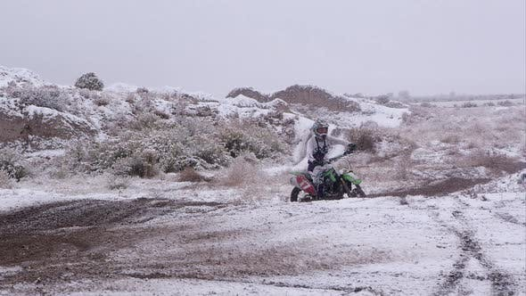 Thumbnail for Man riding motorcycle in snowy desert.