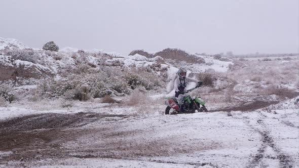 Thumbnail for Mann auf dem Motorrad in der verschneiten Wüste.