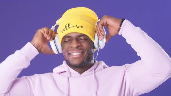 Thumbnail for Cute African-American Man in Headphones Dressed in Street Style Wear, Listening To Music