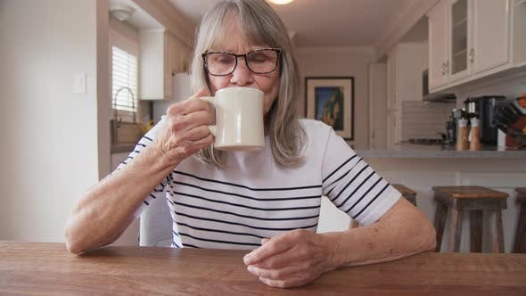 Senior woman drinking her morning coffee while sitting at kitchen table