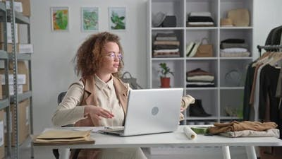 Young Female Small Business Owner Designs Clothes for Sale While Sitting at Laptop in Clothing Store