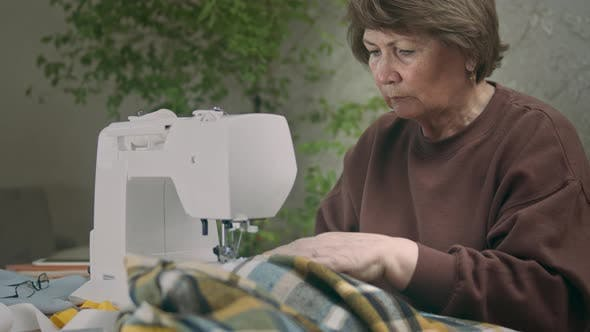 Senior Woman Is Sewing At Home