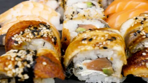 Dolly Footage of Traditional Sushi Rolls on Black Stone Plate