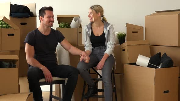 Thumbnail for A Happy Moving Couple Sits on Chairs, Holds Hands and Smiles at the Camera in an Empty Apartment