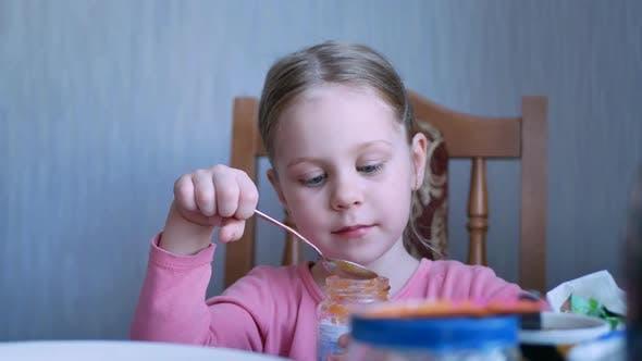 Thumbnail for Adorable Happy Child Girl Eating Fresh Fruit Puree