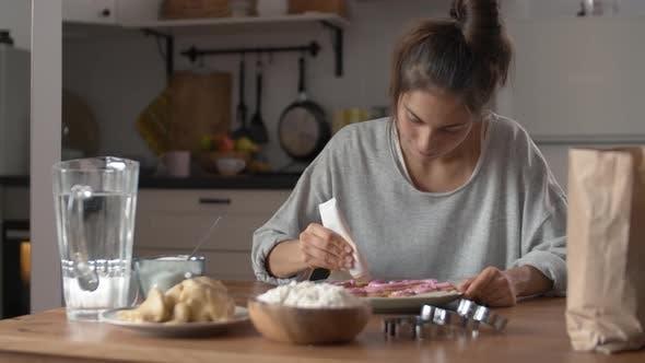 Thumbnail for Junge Hausfrau Dekorieren Kekse zu Hause