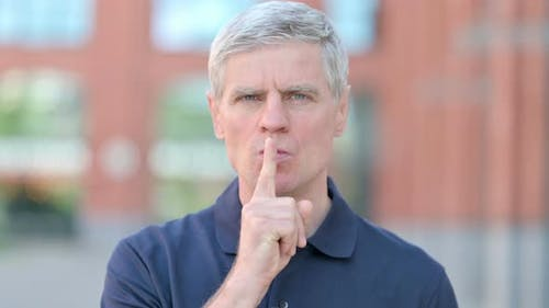 Outdoor Portrait of Middle Aged Man Putting Finger on Lips