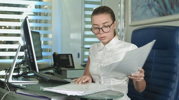 Thumbnail for Hard working businesswoman with laptop and paperwork