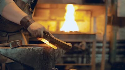 Blacksmith Brushes the Metal with a Brush on the Anvil