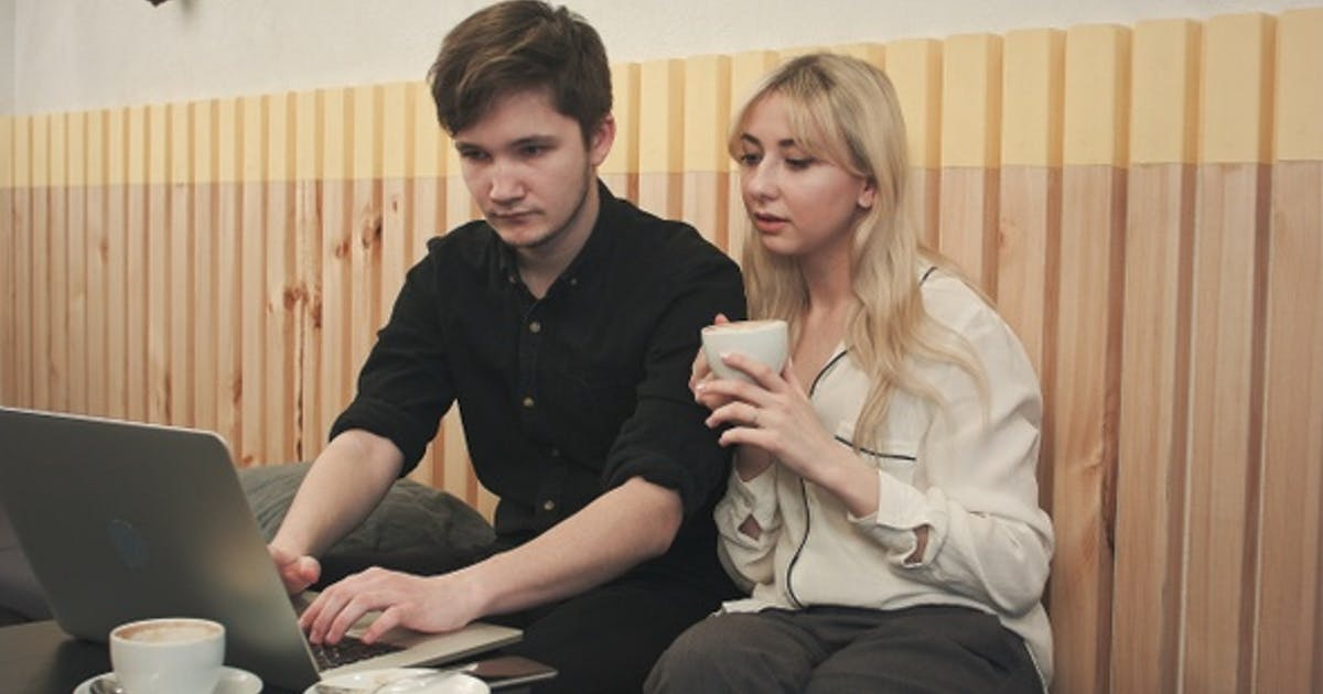 Couple Working on Laptop, Drinking Coffee at Cafe