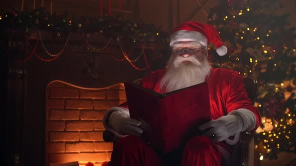 Cover Image for Realistic Santa Clause Sitting Near Fireplace and Christmas Tree, Opening a Large Magical Book with