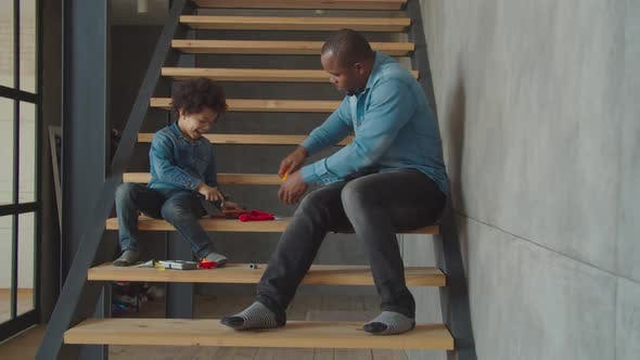 Caring Dad Teaching Son To Use Work Tools at Home