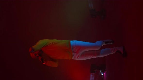 Thumbnail for Vertical Video. A Rap Artist Sings Into a Microphone and Dances in Neon Light and Bright Strobe
