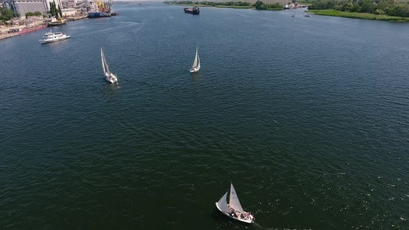 Thumbnail for Aerial Shot of Sportive Yachts Going in the Dnipro River on a Sunny Day