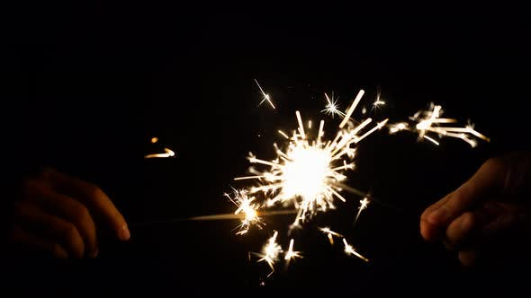 Thumbnail for Hands Playing with Burning Sparklers in Darkness