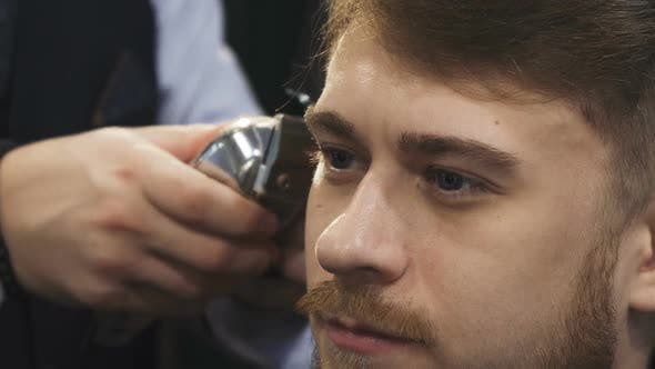 Cover Image for Close Up of a Young Man Getting a Gaircut at the Barbershop