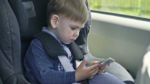 Little Boy Using Smartphone in Car Seat