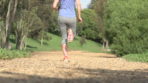 A woman running on a wood chip trail