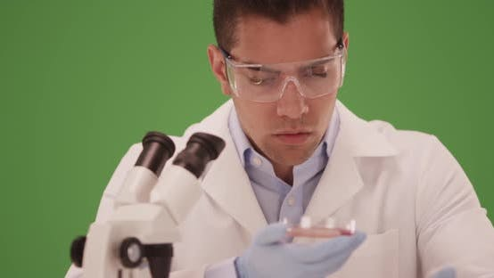 Thumbnail for Millennial Latino medical research scientist studying petri dish on green screen