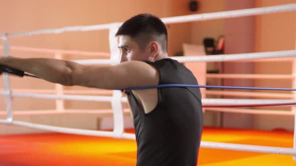 Thumbnail for Man Doing Punches with Resistance Band in Boxing Gym