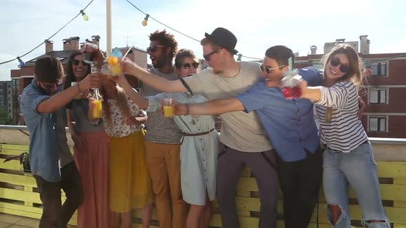 Cheerful multi-ethnic friends standing at rooftop and toasting towards camera