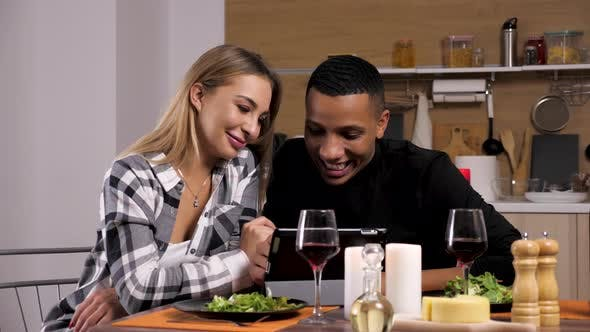 Thumbnail for Happy Smiling and Laughing Interracial Couple Looking at Digital Tablet PC